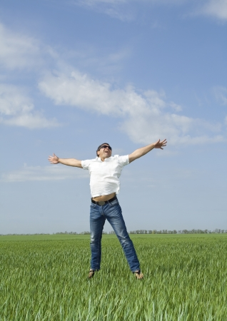 young man jumping a green field of grass 