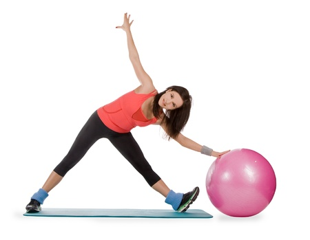 Attractive young female with fitness ball in stretching