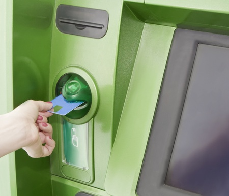 cashpoint: Female inserts a plastic card in the ATM
