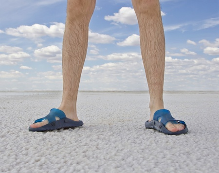 flip flops: tanned legs of man wearing flip flops standing on the beach Stock Photo