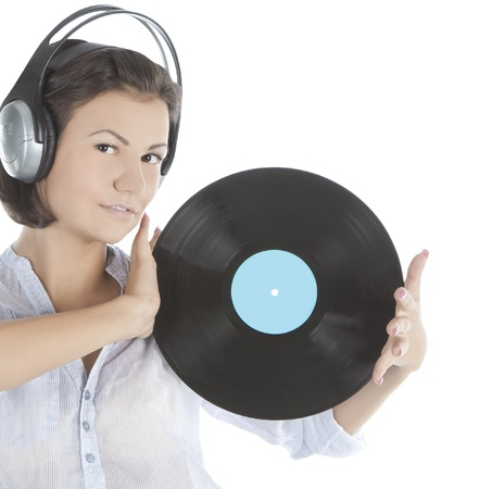 emotional brunette in headphones with vinyl record over white photo