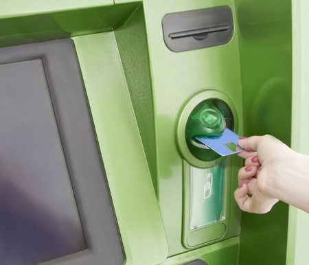 automatic teller machine: Female inserts a plastic card in the ATM