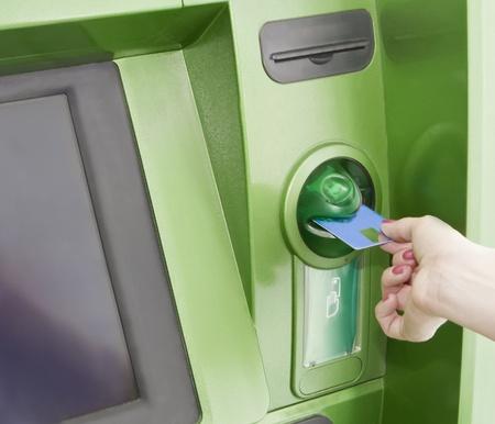 automatic transaction machine: Hembra inserta una tarjeta de pl�stico en la ATM