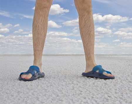 tanned legs of man wearing flip flops standing on the beach photo