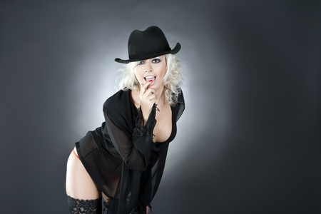 blonde fashion woman portrait wearing black hat over dark Stock Photo