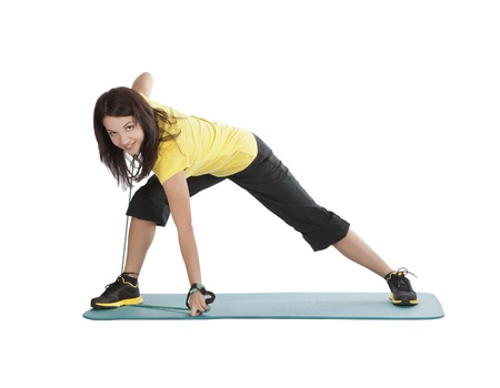 Attractive young female with fitness expander in stretching Stock Photo - 10197290