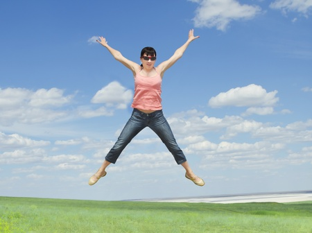 pretty young woman jumping on green grass over blue sky photo
