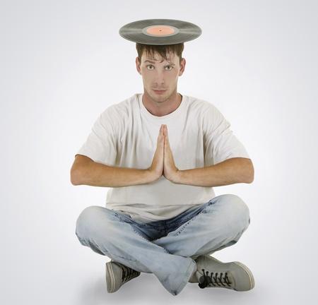 DJ sitting on the floor with vinyl on his head photo