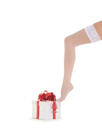 woman leg in white stockings with gift over white photo