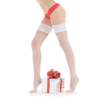 Wonderful female in santa hat and white stockings with christmas gift Stock Photo - 10881236