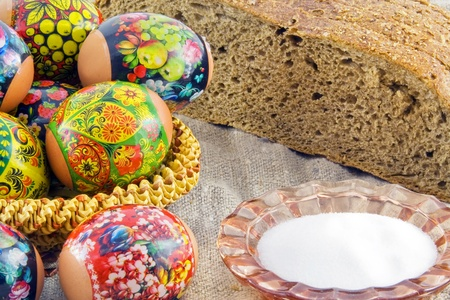 easter eggs in a basket with bread and salt on a rough fabric photo
