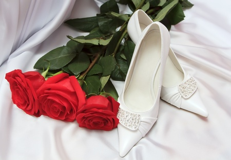 Elegant wedding shoes with red roses photo