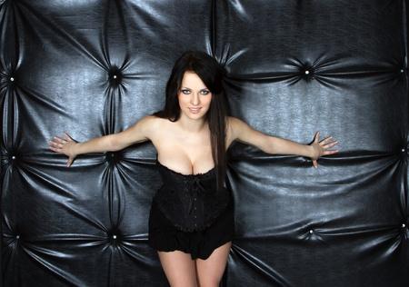 Woman in black corset posing over black  photo
