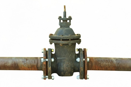 stop gate valve: old rusty pipe with shut-off valve over green grass Stock Photo