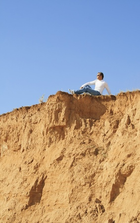 young caucasian man sitting alone over the rock photo