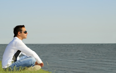 young caucasian man sitting alone and looking to the sea Standard-Bild