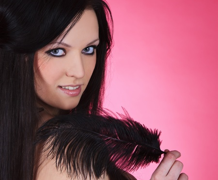 attractive young female with black feather over pink background photo