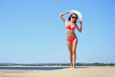 Tanned yound woman posing at the beach photo