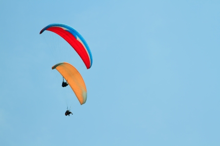 Paragliding over the mountains against clear blue sky photo