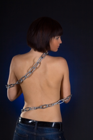 Sexy brunette with bare back in chains over black background photo