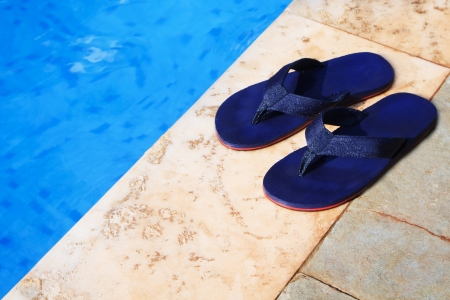pair of blue flip flops at the edge of a swimming pool Stock Photo - 21824981