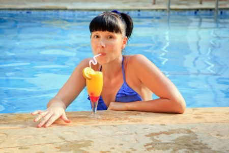 Young brunette drinking cocktail in the pool photo