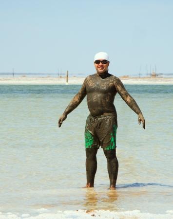 man takes a mud bath in the salty lake Baskunchak photo