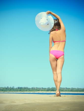 woman in pink bikini with white hat on the beach photo