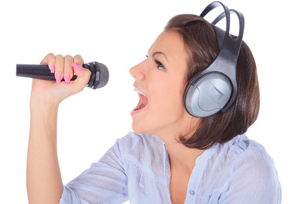 Caucasian female singing in to microphone. photo