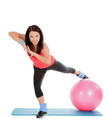 Attractive young female with fitness ball in sport center photo