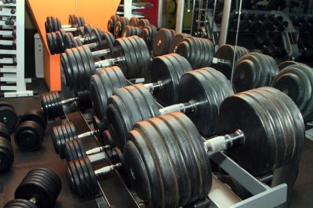 Dumb bells lined up in a fitness studio. Shot focus Imagens