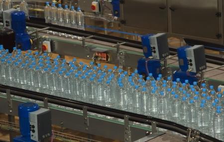 ensamblaje: Botellas de plástico de agua sobre cinta transportadora y la industria embotelladora de agua