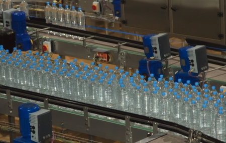 business life line: Plastic water bottles on conveyor and water bottling machine industry