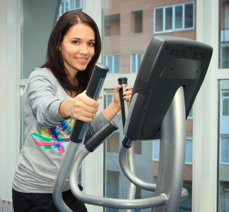 young woman doing exercise on a elliptical trainer photo