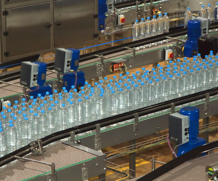 Plastic water bottles on conveyor and water bottling machine industry photo