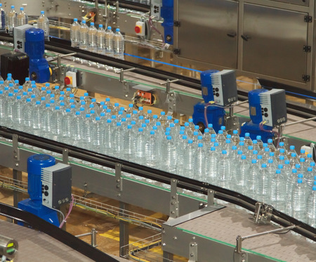 food drink industry: Plastic water bottles on conveyor and water bottling machine industry