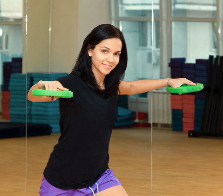 Young woman doing exercise with dumbbells photo