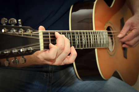 performer playing on the acoustic guitar photo