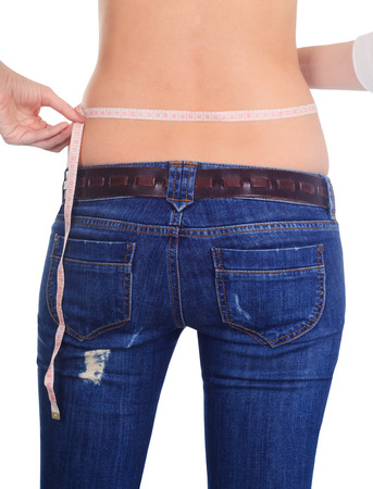 Woman measuring her waist back view over white photo