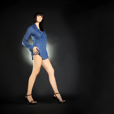 Fashion brunette with long legs posing in the dark photo