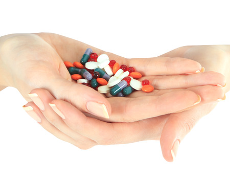drug use: Stack of different pills in woman hands isolated over white Stock Photo