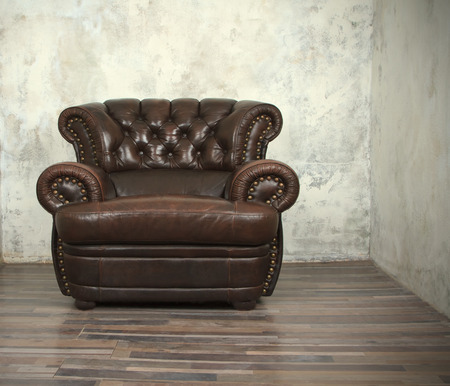 elbow chair: Old vintage brown leather chair in empty room