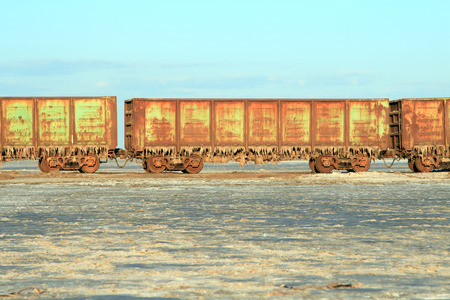 Old rusty train cars with stalactites of salt in the lake Baskunchak