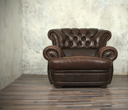 leather chair: Old vintage brown leather chair in empty room