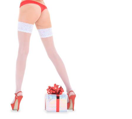 Wonderful female in santa hat and white stockings over Christmas gift photo