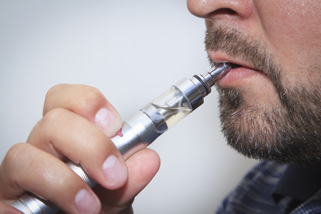 Profile view of man smoking electronic sigarette close up Imagens