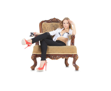 Fashion blonde in red shoes sitting in throne photo