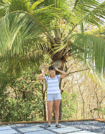 atractive: Happy young woman standing under a palm tree with two leaves
