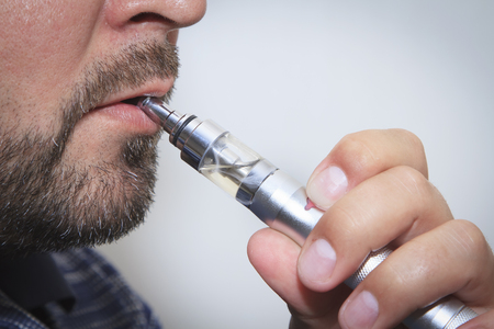 Profile view of man smoking electronic sigarette close up Stock Photo