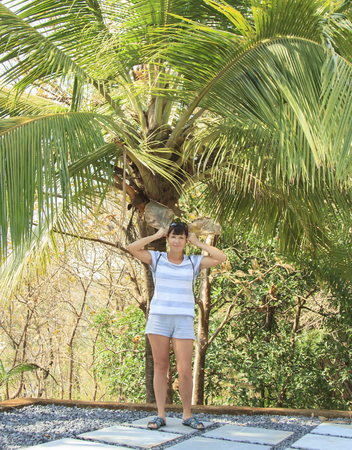 hellion: Happy young woman standing under a palm tree with two leaves